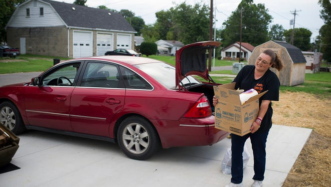 After months of packing and planning, Crystal Causey, unloads boxes into her new home on Fifth Street in Henderson, Monday, Aug. 8, 2016. Causey feels the new neighborhood is safer for her family.