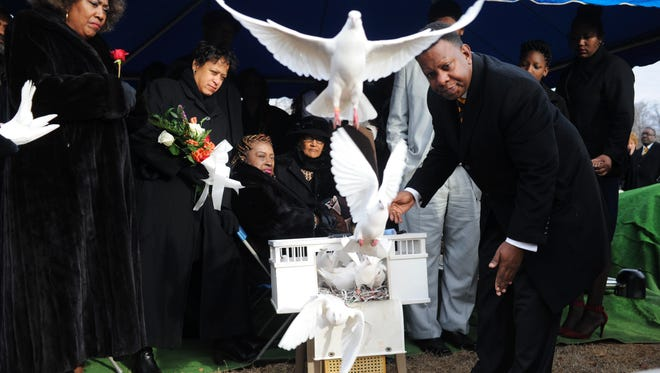Sheryl Rollins, third from left, the widow of civil rights pioneer Avon Rollins Sr., watches as doves are released after a graveside service Dec. 16, 2016, at Mount Olive Cemetery. Releasing the doves is Brian L. Buckmon, owner of Patton Funeral Home.