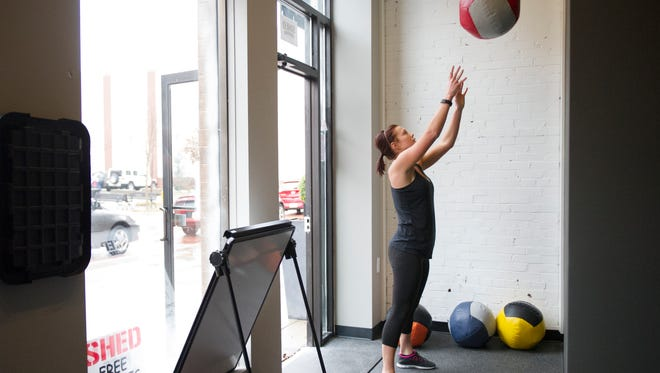 Shelby Winiger does a wall ball shot during one of her high intensity intervals at a class at Shed Fitness. Shed Fitness, located at 203 Main St. in downtown Evansville, is a boutique style gym offering classes and personal training. The gym offers classes for up to 30 people in an intimate setting that promotes a team atmosphere.