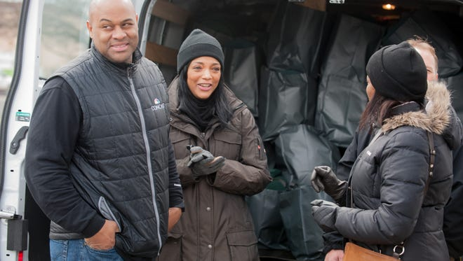 Reggie (left) and Yvette Anderson (center) of Jackson distributing goods in Asbury Park.