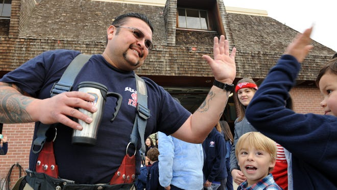 Salinas Fire Department Engineer Paul White gets a high-five from Sacred Heart students on Wednesday. As part of Catholic Schools Week in Salinas, students brought cookies and handmade gift cards to the firefighters as thanks for their service.