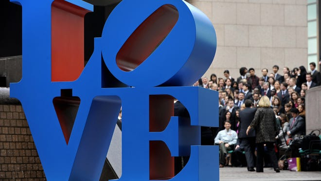 "A sculpture by US artist Robert Indiana is displayed in a public area in Hong Kong on March 9, 2008 as people (background) gather for a group photo.  The sculpture is inspired from Indiana's ""Love"" painting from the 1960s.  AFP PHOTO/PHILIPPE LOPEZ (Photo credit should read PHILIPPE LOPEZ/AFP/Getty Images)"