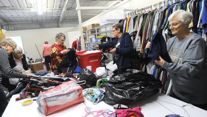 Volunteers sort through clothing donations at the new Love and Care Ministries building in Clyde.