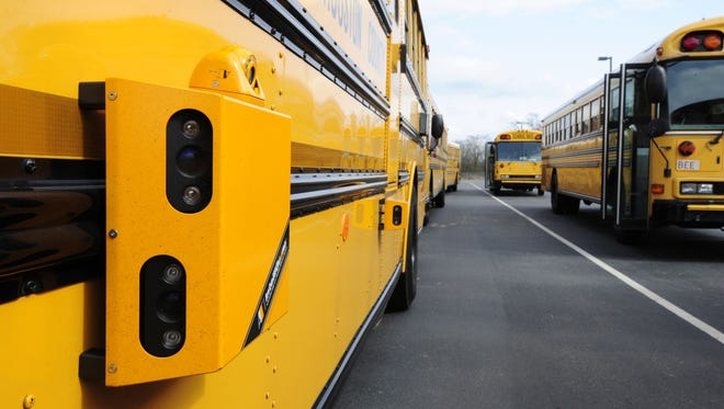 Pictured is a school bus equipped with stop arm signal camera system mounted on the outside. The cameras have sensors that make photographs of vehicles and drivers that pass the bus when the stop arm signal on the bus is deployed.