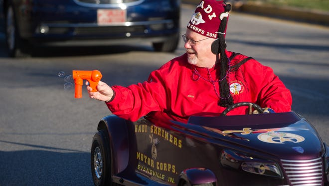 Andy Stewart with the Hadi Shriners Motor Corp. shoots bubbles at the crowd as he makes his way down Franklin Street in the Grand Parade, the Franklin Street Events Association's celebration of Mardi Gras down Franklin Street in Evansville, Ind. Saturday afternoon, Feb. 25, 2017.