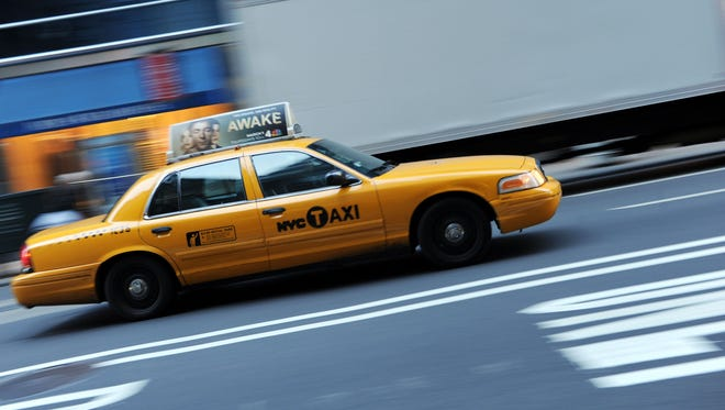 A file photo taken on Feb.y 28, 2012 shows a New York yellow cab taxi driving up Fifth Avenue. Yellow taxi cabs have significantly fewer accidents than cabs of a darker hue, according to new research.