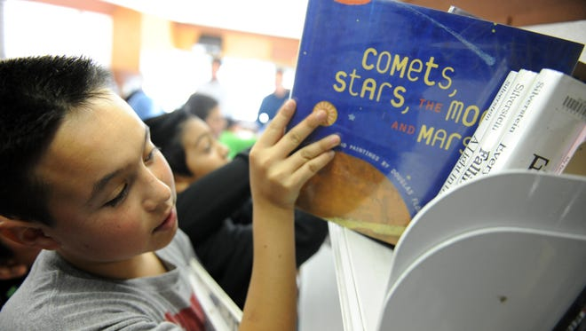 Nathan Ortega, 11, checks out the selection on Tuesday during a Salinas Public Library Bookmobile visit to the Oasis Charter Public School.
