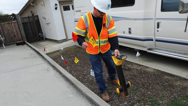 At a Creekbridge homeowner's request, PG&E's Mat VanSant, a gas compliance representative, locates and marks a gas line using a sophisticated sensor. The line lies between the red and yellow flags.