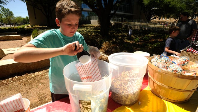 Twelve-year-old Jaxton Cranfill, owner of Jaxs Sweet Snaxs, fills bags with popcorn during the Abilene ChildrenÕs Business Fair on Saturday, April 8, 2017, at Abilene Christian University.