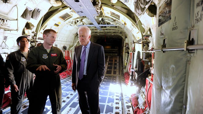 Capt. Ryan Clayburn (center) explains how tight things can get in the cargo bay of a C-130J aircraft when fully loaded and his mission while piloting the aircraft to U.S., Sen. John Cornyn (right).  Cornyn toured the Abilene air base in April 2017.