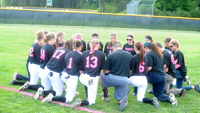 The Wilson Memorial softball players say a team prayer before the start of Tuesday's game with Stonewall Jackson. The game raised awareness and money for cancer research.