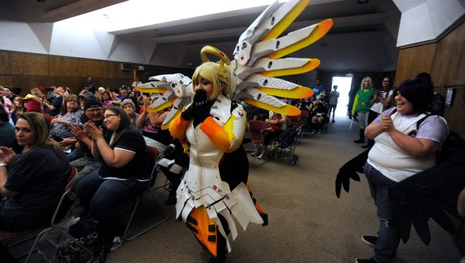 """Josie Medina, dressed as Mercy from the video game, """"Overwatch"""" reacts after her name is called as the winner in the adult costume contest at LibCon on Saturday, May 6, 2017, at the main branch of the Abilene Public Library."""