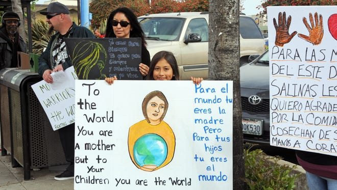 Judith Caudillo, 9, holds a beautiful handmade sign at the Mother's Day March in east Salinas.