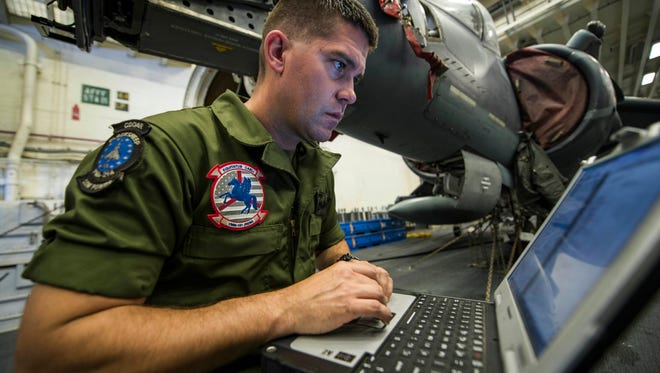 Staff Sgt. Kevin Brandt, a native of Green Bay assigned to the 15th Marine Expeditionary Unit, checks a maintenance list in the hangar bay of the amphibious assault ship USS America on May 13. More than 1,800 Sailors and 2,600 Marines assigned to the America Amphibious Ready Group and the 15th MEU are training off the coast of Southern California in preparation for the group's deployment later this year. America ARG comprises America, the amphibious dock landing ship USS Pearl Harbor and the amphibious transport dock ship USS San Diego.