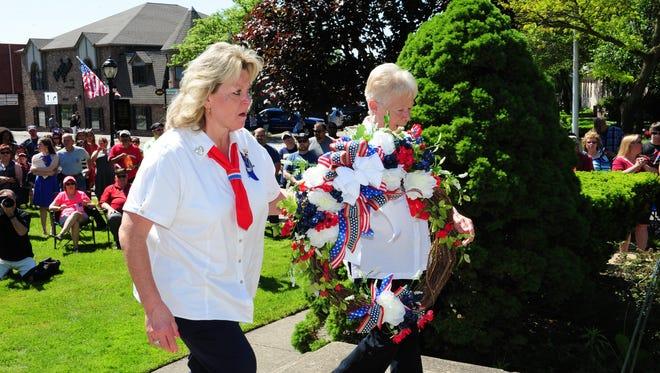 American Legion Post 346 Ladies Auxiliary past president, Tammy Festian and president Leah Branchau present the memorial wreath in Farmington on Memorial Day.