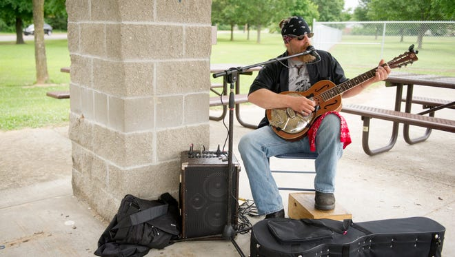 Ryan Rigdon plays the blues as he takes part in the Arts Council of Southwestern Indiana SummerSong evening in Price Park last summer. The hour long performance highlighted local performers in 29 different parks around the city.