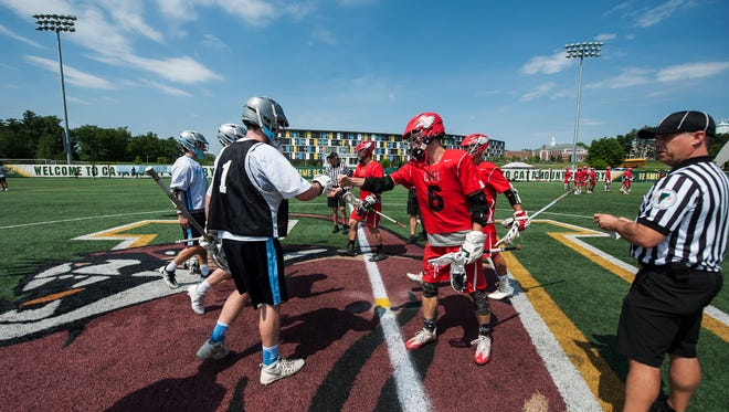 The captains meet at center field during the Division I boys lacrosse championship game between the Champlain Valley Union Redhawks and the South Burlington Rebels at UVM's Virtue Field on Saturday June 10, 2017 in Burlington.