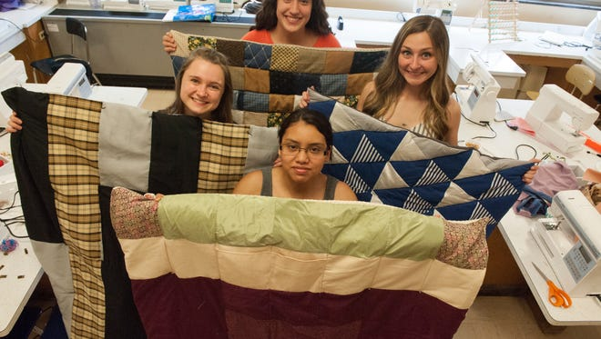 Diana Morales, front, Shiann Wilson , left, Lyly Hogan, right, and Rachel Ricci, show their finished quilts at the sewing class at Millville High School. Students in the Sewing I class at Millville High School have been making lap quilts for veterans living at the New Jersey Memorial Home at Vineland.