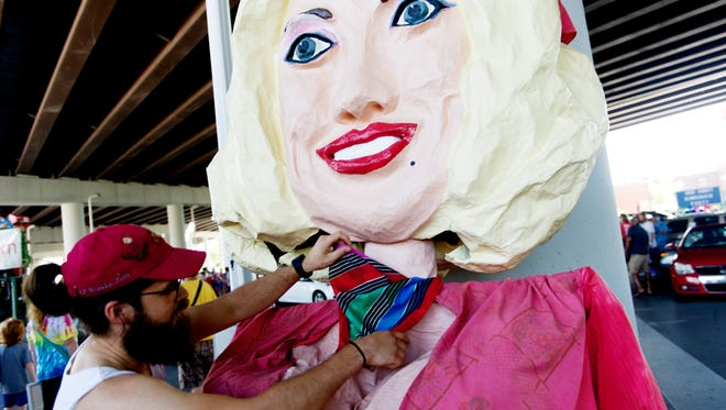 Andreas Bastias, of Knoxville, puts a bandanna around a Dolly Parton puppet during the annual Knoxville Pridefest parade in 2017.;