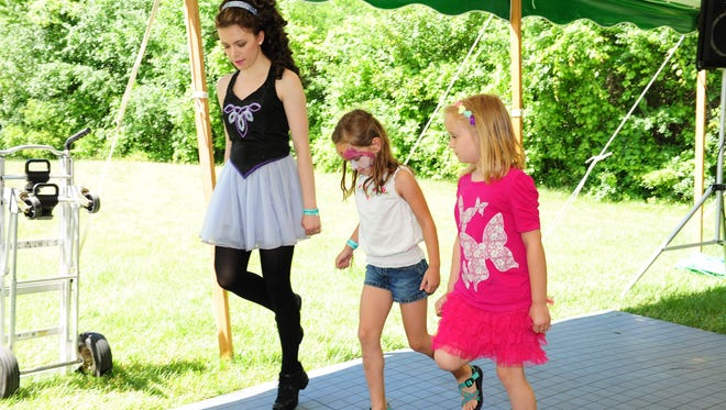 Motor City Irish Dance school instructor Jillian Wolf teaches Alyse Ostroskie of Livonia and Genevieve Parnin of Farmington the traditional Irish dance techniques at this year's eighth annual Motor City Irish Fest at Greemead in Livonia.