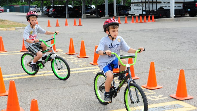 Livonia brothers Andrew and Nik Grzanowski learn about bike safety as they ride around the course during the annual Passport to Safety event.