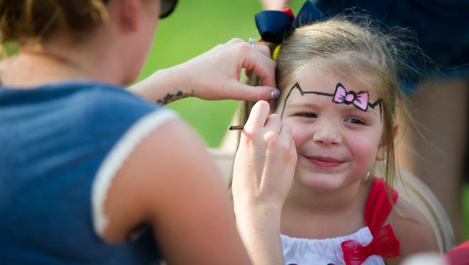 Three year-old Lucy Busing (right) of Boonville gets a Hello Kitty painted on her face by Jaclyn Cardin in 2015 at the Fourth of July Celebration in Newburgh.