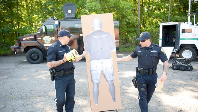 The Bergen County Police Department bring out their fleet of emergency and armored vehicles in this august 2014 file photo for inspection at the Bergen County Law and Public Safety Institute Thursday. Bergen County police officers Lt. Frank Carrafiello (l) and Vincent Mayo (r) prepare a target for a taser demonstration.