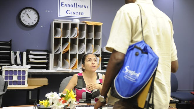 Metro Schools enrollment specialist Wanda Feliciano helps a parent on Saturday, July 22 at the Global Mall Enrollment Center in Nashville, Tenn. The district opened up a pair of enrollment centers on the weekends to help make it easier for working parents to enroll.