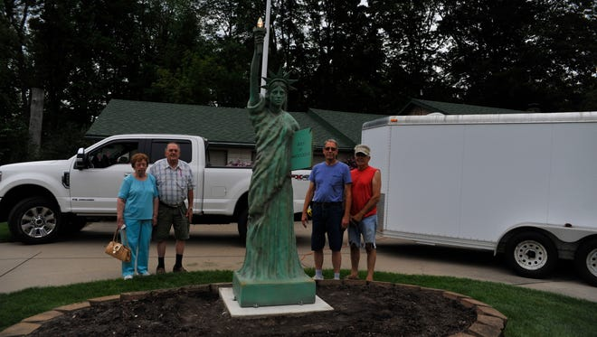 From left, Helen Haydock, Herb Haydock, Jim Koehntopp and Dave Yonkovich pause with the Haydocks' new 9-foot version of the Statue of Liberty after it was installed Friday. Owning a copy of the statue has been her husband's dream, Helen Haydock said.