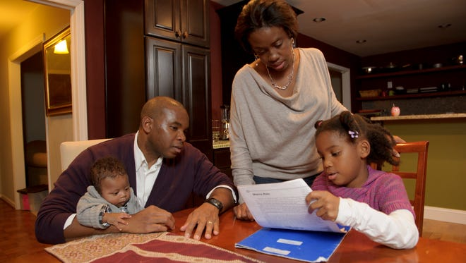 Kevin Powell, with son J. Davis, and wife Rachel help daughter Kaylee with her homework in Atlanta.