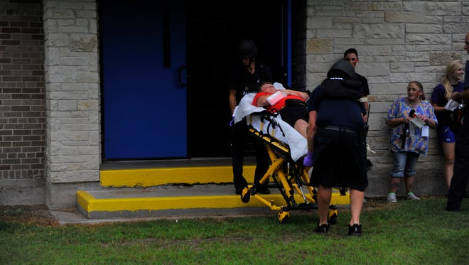 "Medics bring a ""shooting victim"" out of the Assumption High School gymnasium Thursday morning while other volunteer victims look on."