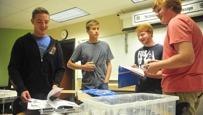 Bucyrus students, from left, Austin Johns, Garett Jackson, Jonathon Shultz and Randall Elchert look over new robotics equipment Wednesday on their first day of school.