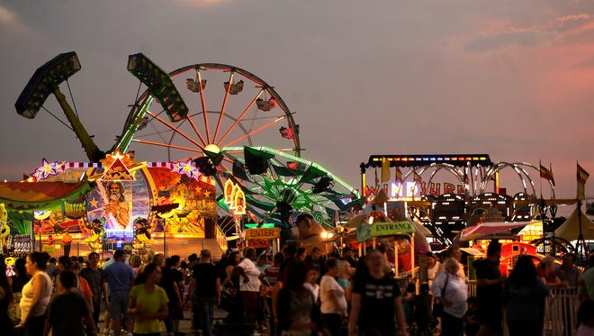 The sun sets as fair patrons walk the midway during last year's West Texas Fair & Rodeo's Sneak-A-Peek.