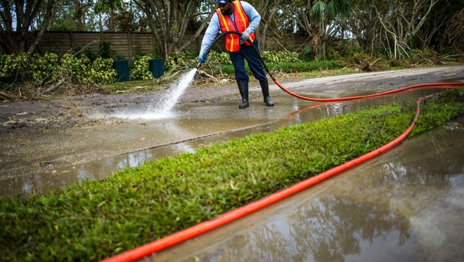 Darryl Jones, of St. Petersburg, sprays sewage from Mahogany Bend Drive into a vacuum truck in Naples on Thursday, Sept. 14, 2017.