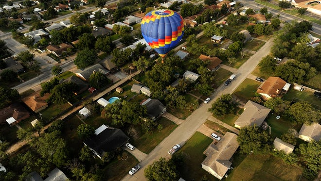A balloon flies over a neighborhood near Buffalo Gap Road during the morning flight of the 2015 Big Country Balloon Fest.