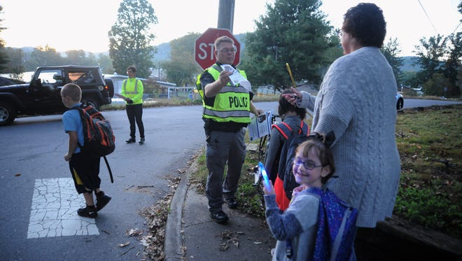 Parents and children make their way east on First Street before crossing the road on their way to Black Mountain Primary during Walk to School Day Oct. 4.