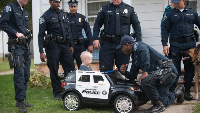From left, Camden County Police Officers, Denis Smarth, Sherrod Paterson, Michael Agron, Michael Shirk, William Ramos and Allan Williams, kneeling down interact with 3-year-old Ben Graham in his new K-9 Police car at his home in Elmer. Camden County Police surprised Ben with a special K9 demo.