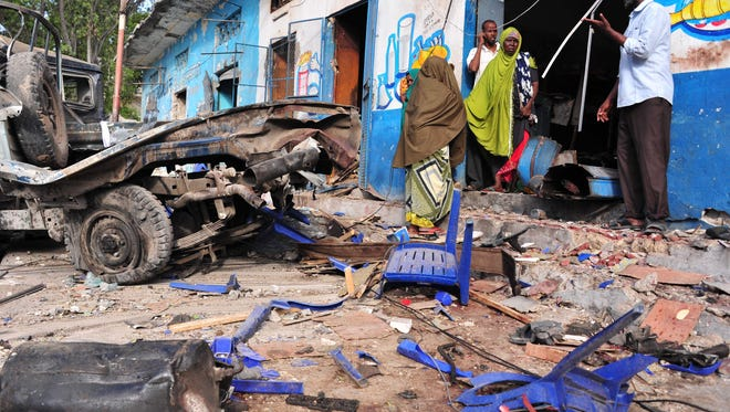 Residents walk at the scene of a blast on Oct. 29, 2017, a day after two car bombs exploded in Mogadishu.