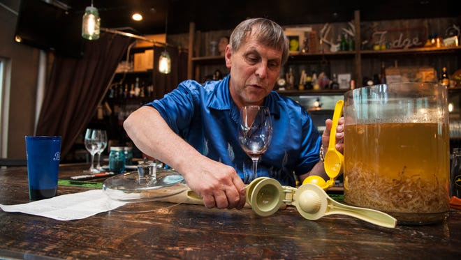 David Engel trades out an old lemon squeezer for a new one before sieving the ginger out of the vodka infusion. The ginger is featured in one of the many specialty drinks available at a(Muse.) in Rehoboth.