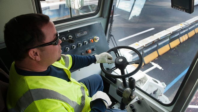 Delaware River Port Authority employee Jose Heredia drives the Zipper machine on the Camden side of the Ben Franklin Bridge. The machine moves the barrier that separates the westbound and eastbound lanes of traffic.