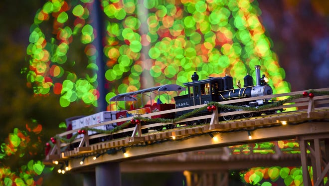 A train passes over one of five bridges that are part of the Holiday Model Train Show at the Atlanta Botanical Garden.