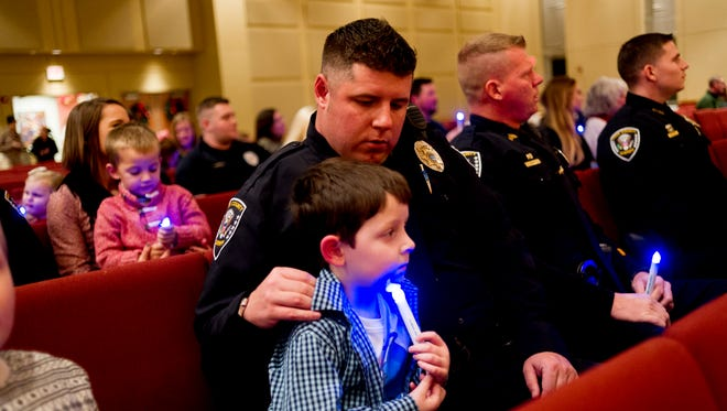 Knox County Sheriff officer Nathan Stachey holds son Easton, 5, during a Project Blue Light ceremony at Farragut United Methodist Church in Farragut, Tennessee on Saturday, December 9, 2017. The ceremony honored active officers and those who have fallen in the line of duty.