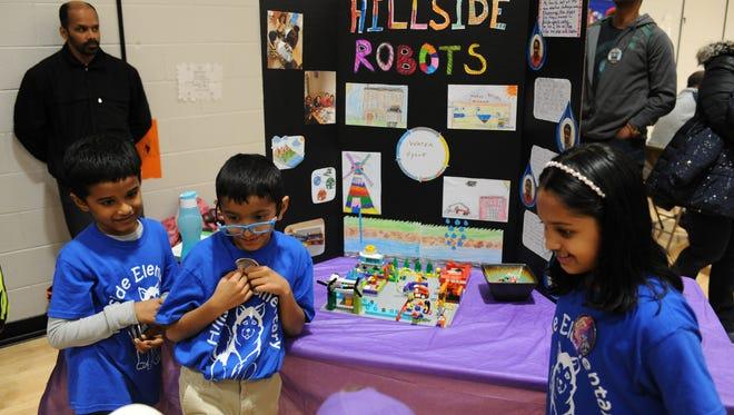 Hillside Elementary students Mathew Eruppakkattu, Neil Abraham and Ananya Anoop take questions about their robotics display.