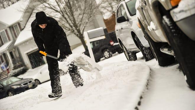 Mac Shahin shovels snow from his sidewalk on Heritage Drive  in Englishtown on Saturday, Dec. 30.