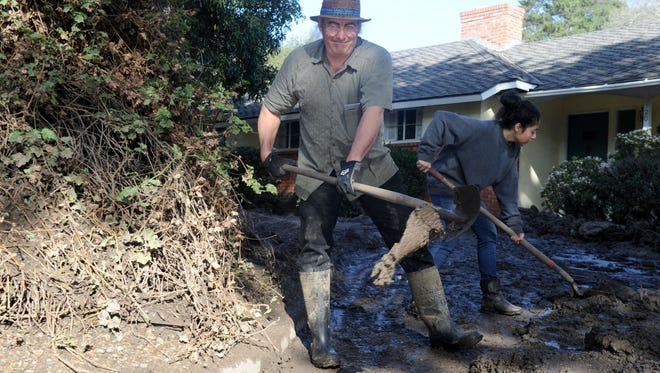Mark Vance and his daughter Kristy shovel some mud out of their driveway on Olive Mill Road in Montecito on Wednesday.