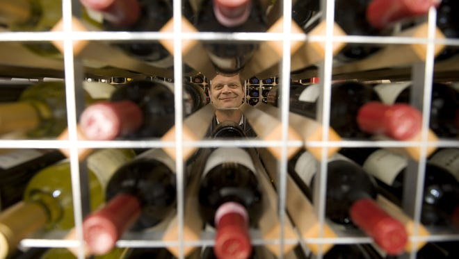 Moore Brothers Wine Company co-owner David Moore peers through bottles of wine stacked in his Pennsauken shop in this 2009 photo. The store keeps its temperature at 56 degrees to protect its wine stock.