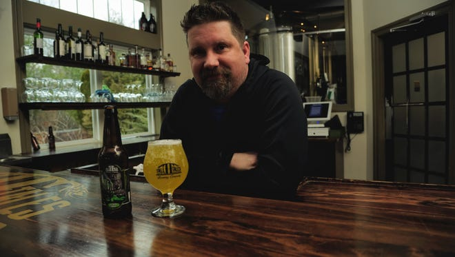 Eric Camper, head brewer at Tall Tales poses with Key'd from his Liquid Denial special release series.