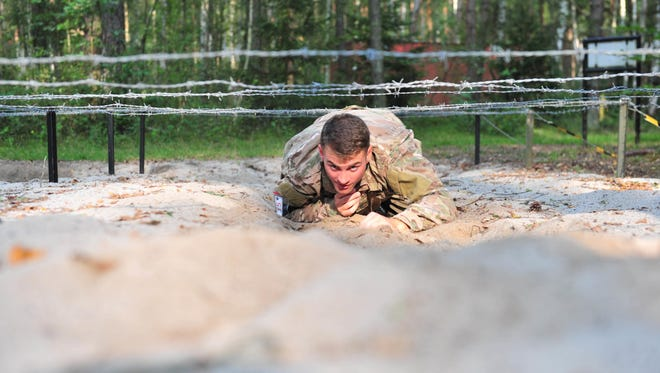 U.S. Army 1st Lt. Bond Finseth, assigned to U.S. Army Africa, crawls beneath wires on an obstacle course during the 2017 European Best Warrior Competition on Aug. 21 at Grafenwohr Training Area, Germany.