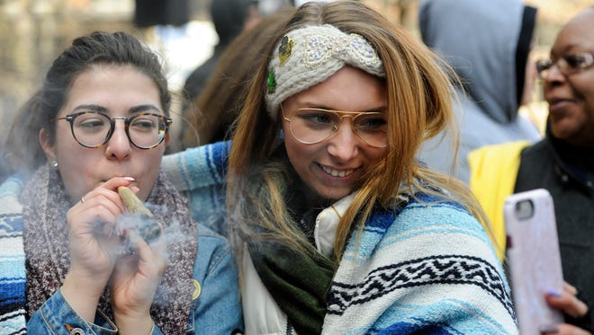 Raquel Cooprider of Ypsilanti, left, smokes a shared joint as her friend Victoria Siesky of Ann Arbor takes a selfie of the both of them during Hash Bash in Ann Arbor. The University of Michigan released a study on Wednesday that said marijuana use among college students is the highest it has been in three decades.