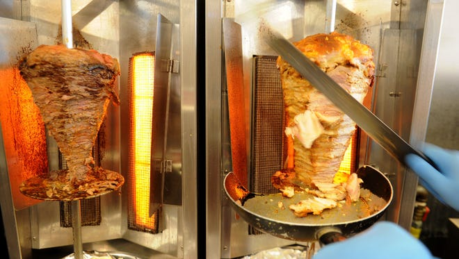 Mazen Naddour, owner of Azi Grill in Thousand Oaks, cuts away at the roasted chicken from the rotisserie.